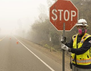 Pacific Power employee Nick Shaffer wears a face mask to protect against wildfire smoke as he directs traffic on Route 22 state highway in Oregon, September 2020.